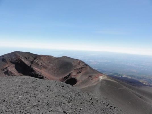 Fahrt mit der Seilbahn auf den Ätna-Hauptkrater. Achtung: Auf 3000 Metern über Meer ist es selbst im brütenden Hochsommer sehr kalt und windig. Die phänomenale Aussicht und die bizarre schwarze Vulkanlandschaft sind das lange Anstehen mit den Touristenmassen wert.