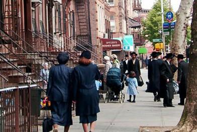 Geschäfte und Schulen sind plötzlich auf Hebräisch angeschrieben. Mann trägt Hut, Bart und Zöpfe…