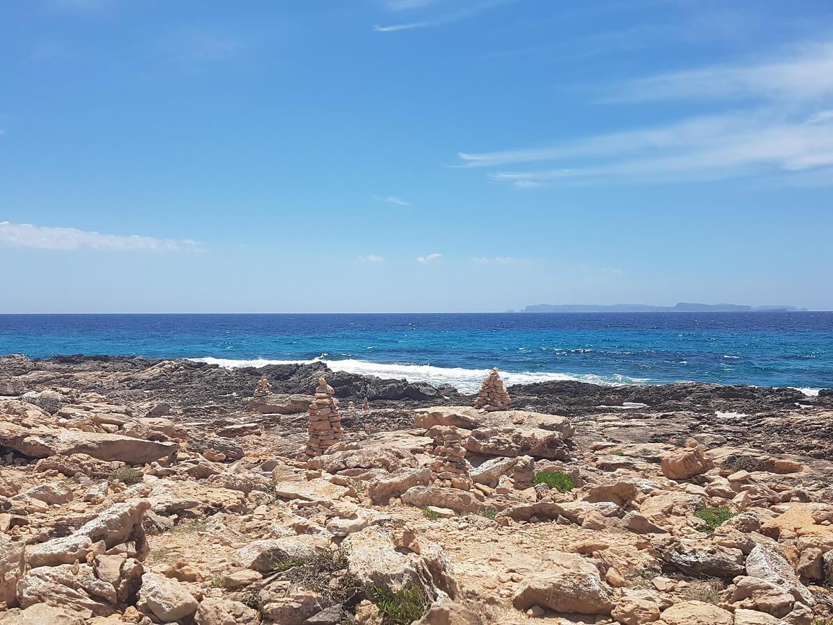 Steintürmchen auf dem Weg zum Strand von Es Caragol